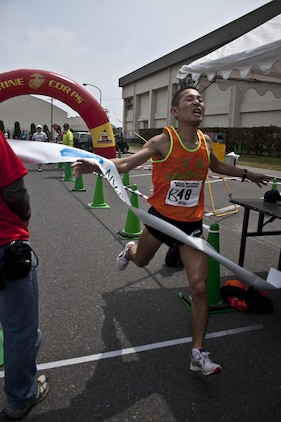 Yoichi Kohno, first place male finisher of the 46th annual Kintai Marathon, crosses the finish line in front of the IronWorks Gym here, April 14, 2013. The event included a full marathon, half marathon, and five-kilometer walk.