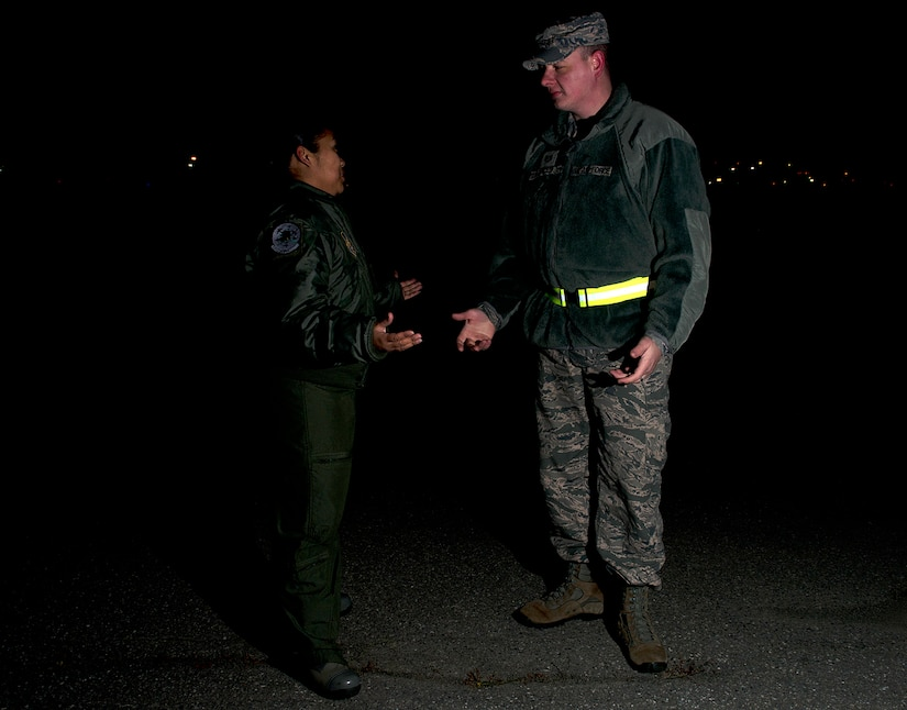 Air Force Staff Sgt. Sheila deVera and Tech. Sgt. Raymond Mills, 673d Air Base Wing Public Affairs photojournalists, demonstrate why wearing a reflective belt to be seen is important. All uniformed military members on Joint Base Elmendorf-Richardson are required to wear reflective belts or a reflective material while outside on base during hours of darkness and inclement weather. Safety officials urge everyone, whether in uniform or not, to abide by this policy. The material used to create a reflective belt bounces light back at the source, making it easier for drivers to see pedestrians and cyclists. A reflective belt is not required while wearing Air Force physical training uniforms, since it is made with reflective material, but Army PT uniforms require reflective belts. JBER instruction 91-202 explains, in detail, when and where reflective belts must be worn, but a good rule of thumb is if it is less than full daylight conditions, wear the belt. (U.S. Air Force photo/Staff Sgt. Zachary Wolf)