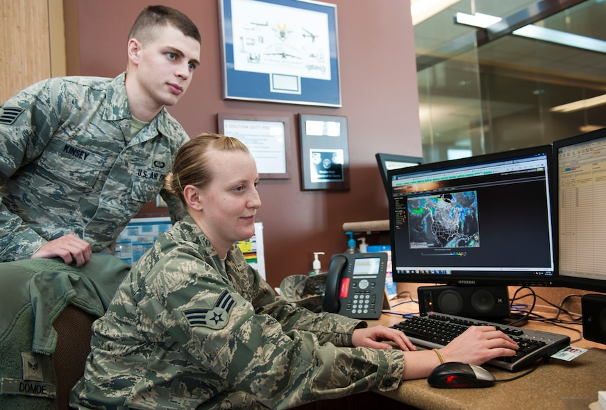 Staff Sgt. Zak A. Kinsey, 5th Operations Support Squadron noncommissioned officer in charge of mission weather, checks the work of Senior Airman Courtney Domoe, 5th OSS weather forecaster, Oct. 23. The Weather Flight is currently preparing for the harsh North Dakota winter ahead. Their forecast accuracy is crucial for mission readiness. (U.S. Air Force photo/Airman 1st Class Apryl Hall)
