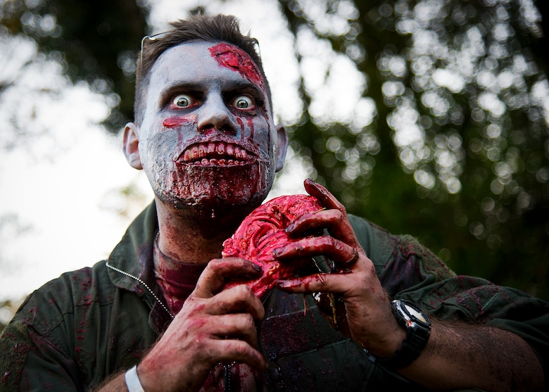 A zombie dines on the brain of some unlucky runner during the 2nd Annual Zombie Run Oct. 26 at the Eglin Air Force Base golf course.  More than 500 people attempted to outrun zombies and maneuver through various obstacles along the four-mile course.  (U.S. Air Force photo/Samuel King Jr.)
