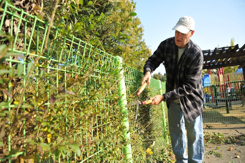 Senior Master Sgt. Lee Schmidt, 51st Munitions Squadron first sergeant, clips hedges at Mustang Valley Park at Osan Air Base, Republic of Korea, Oct. 26, 2013. The 51st Civil Engineer Squadron provided all the tools and equipment for volunteers to use during the clean-up. (U.S. Air Force photo/Staff Sgt. Emerson Nuñez)