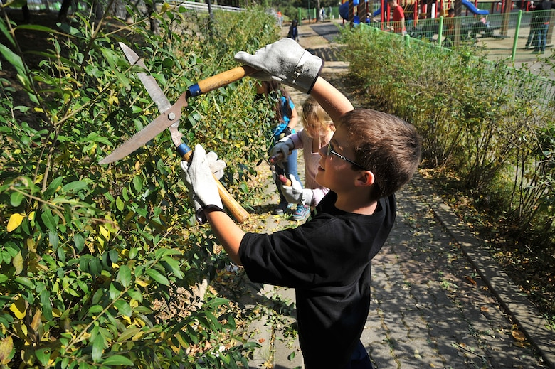 David Honaker, 10, and his sister Katie, 9, clip hedges at Mustang Valley Park at Osan Air Base, Republic of Korea, Oct. 26, 2013. Parents were happy to have their kids take part in making the park a better and safer place. (U.S. Air Force photo/Staff Sgt. Emerson Nuñez)