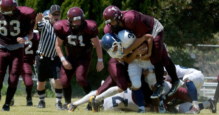 "Charlie Van Allen, a Matthew C. Perry High School Samurai running back and linebacker, tackles a Sotoku High School Fighting Ducks running back during a scrimmage game at the M. C. Perry football field here Aug. 19, 2012. ""I thought we were quite competitive, considering they have been practicing for a year and some of those kids have been together for three years,"" said Frank Macias, Samurai head coach. ""They play semi-pro and college teams as well. We are a brand new program. For most of these kids, this is the first time they have ever hit somebody."""