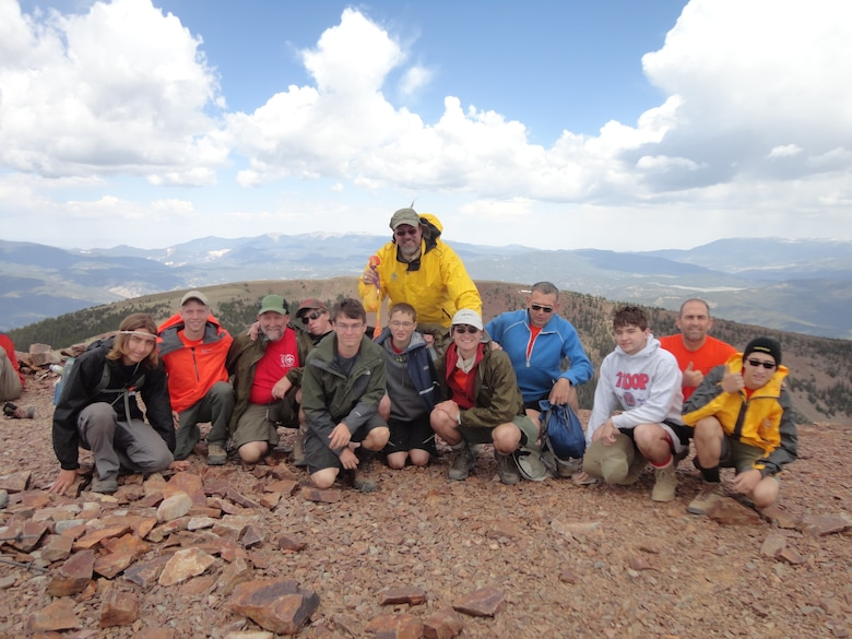 """USACE Park Ranger David Quebedeaux (back, dressed in yellow) and his Boy Scout troop pose with their rubber chicken for a picture on the summit of Baldy Mountain (12,441 feet) in northern New Mexico during their hike at the Philmont Scout Ranch, June 17, 2013. Quebedeaux uses rubber chickens as a fun motivator while the Scouts hike difficult, steep trails in cold weather conditions. The troop packed multiple rubber chickens and gave them out to people they met on the trail who made a positive impression on their group. """"Nobody can resist smiling when they are holding their very own rubber chicken,"""" Quebedeaux said."""