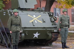 Two Soldiers with the 1st Sqdn., 4th Cav. Regt., dressed in Vietnam-era uniforms, stand in front of an M113 ACAV at an Oct. 18 ceremony to unveil the vehicle. The vehicle, which was originally used in the Vienam War, was restored by Soldiers within the squadron and will sit in front of the squadron's headquarters. (Sgt. Scott Lamberson | 4th IBCT)