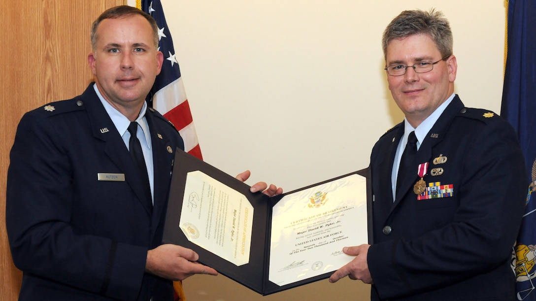 New York Air National Guard Maj. David Pyke (right) receives a Certificate of Retirement from Lt. Col. Charles Hutson, Commander of the 174th Comptroller Flight on 4 October 2013 during a retirement ceremony held at Hancock Field Air National Guard Base, Syracuse, New York. Maj. Pyke also received a Meritorious Service Medal during the ceremony. Maj. Pyke joined the unit in April of 1990. (New York Air National Guard Photo by Senior Airman Duane Morgan)