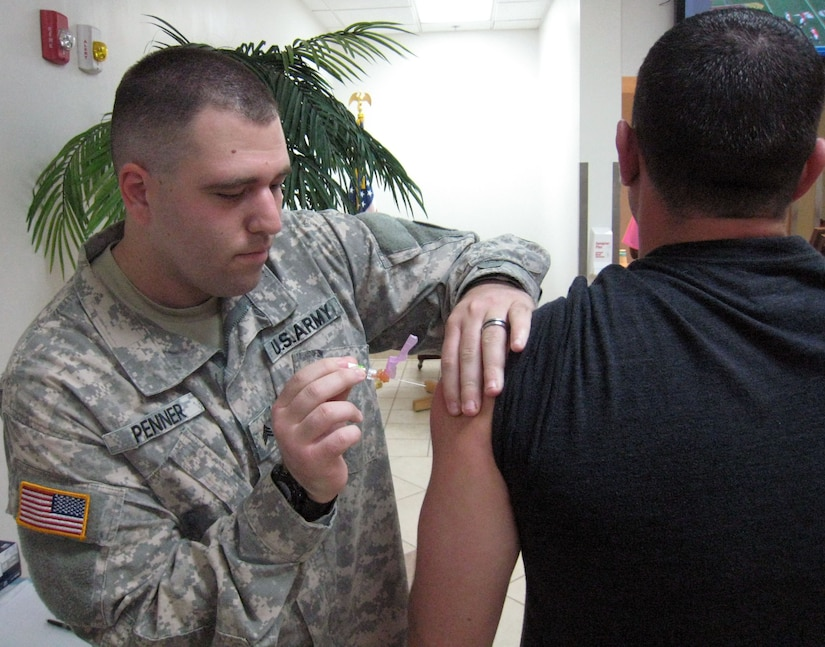 U.S. Army Sgt. Eric Penner administers the flu vaccine to a member of Joint Task Force-Bravo, Soto Cano Air Base, Honduras, Oct. 27, 2013.  Joint Task Force-Bravo's Medical Element (MEDEL) is providing the flu vaccine to all members of the task force in order to prevent the spread of the flu virus.  (U.S. Air Force photo by Capt. Zach Anderson)