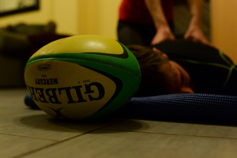 SPANGDAHLEM AIR BASE, Germany--A rugby ball is displayed as Elliot Curtis, a 52nd Force Support Squadron Eifel Arms Inn shuttle driver from Fort Walton Beach, Fla., receives a back massage from his wife Staff Sgt. Charlotte Curtis, a 52nd Judge Advocate paralegal inside their home Oct. 24, 2013. Curtis's wife attends almost every game that he plays in. (U.S. Air Force photo by Senior Airman Rusty Frank/Released)