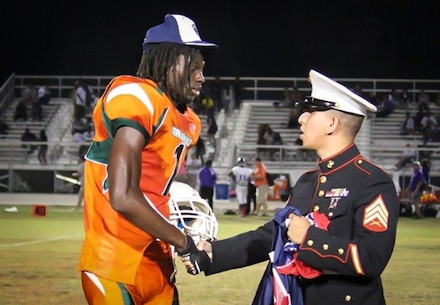 """Marine Corps recruiter Sgt. Mario Sanchez with Recruiting Substation Fort Myers, Recruiting Statin Fort Lauderdale, Fla., presents a jersey to Ryeshene Bronson from Dunbar High School Oct. 11, 2013, for being selected to play in the Semper Fidelis All American Bowl. Bronson, a senior wide receiver at Dunbar, excels in the class room and is a prominent mentor in his community. Selected to play for his character as a whole, Bronson said he is excited about the opportunity and that he is """"ready to go."""""""