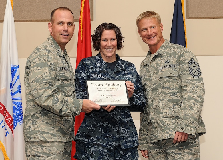 Petty Officer 1st Class Erika Peppler, Naval Information Operations Command, center, receives the Middle Enlisted of the Quarter Award during the 460th Space Wing Quarterly and Team Buckley Awards Oct. 30, 2013, at the Leadership Development Center on Buckley Air Force Base, Colo. (U.S. Air Force photo by Senior Airman Marcy Copeland/Released)