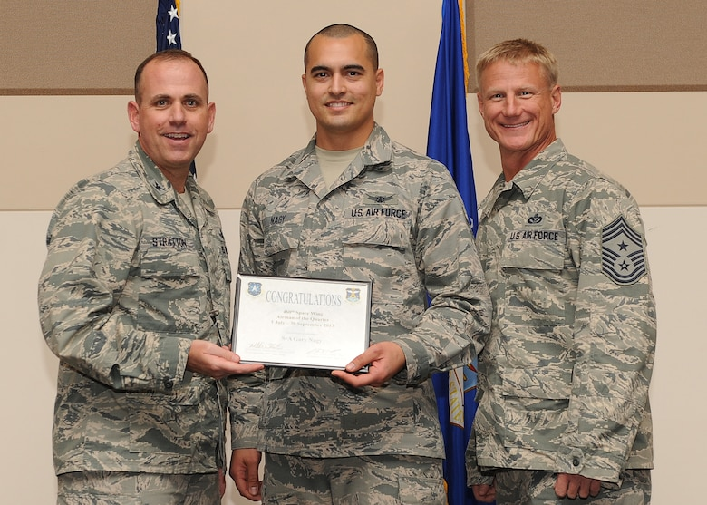 Senior Airman Gary Nagy, 460th Operations Group, center, receives the Airman of the Quarter Award during the 460th Space Wing Quarterly and Team Buckley Awards Oct. 30, 2013, at the Leadership Development Center on Buckley Air Force Base, Colo. (U.S. Air Force photo by Senior Airman Marcy Copeland/Released)