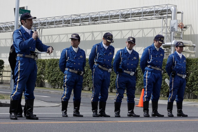 Ida Yoshikazu, Iwakuni police officer, talks to spectators about safety when driving off station on the road adjacent to the outside pool here March 22. Iwakuni police officers did demonstrations on being pulled over out in town and explained the differences between getting pulled over in America and Japan.