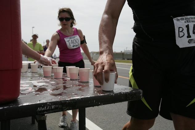 Racers grab water, sports drinks and snacks as they race by a hydration stand during the Kintai Marathon around Marine Corps Air Station Iwakuni April 15, 2012. Stands were placed along the track to keep runners' bodies in the best condition during the race.