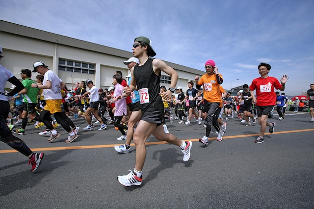 Racers take off from the starting line after setting their watches to help pace themselves for the 45th annual Kintai Marathon around Marine Corps Air Station Iwakuni April 15, 2012. Racers began clumped together, but the pack quickly thinned as many racers sped past or dropped behind the rest of the pack. The race isn't about winning for some competitors; some just love the thought of completing the race. The ability for all of these racers to complete the 26-mile race takes training and keeps these runners fit and healthy.