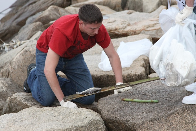 Matthew D. Stover, volunteer, searches between rocks north of Penny Lake on the ocean side of the seawall April 20, 2012, to rid the surrounding area of trash and debris washed ashore aboard Marine Corps Air Station Iwakuni. The volunteers devoted several hours of their mornings to clean the seawall.
