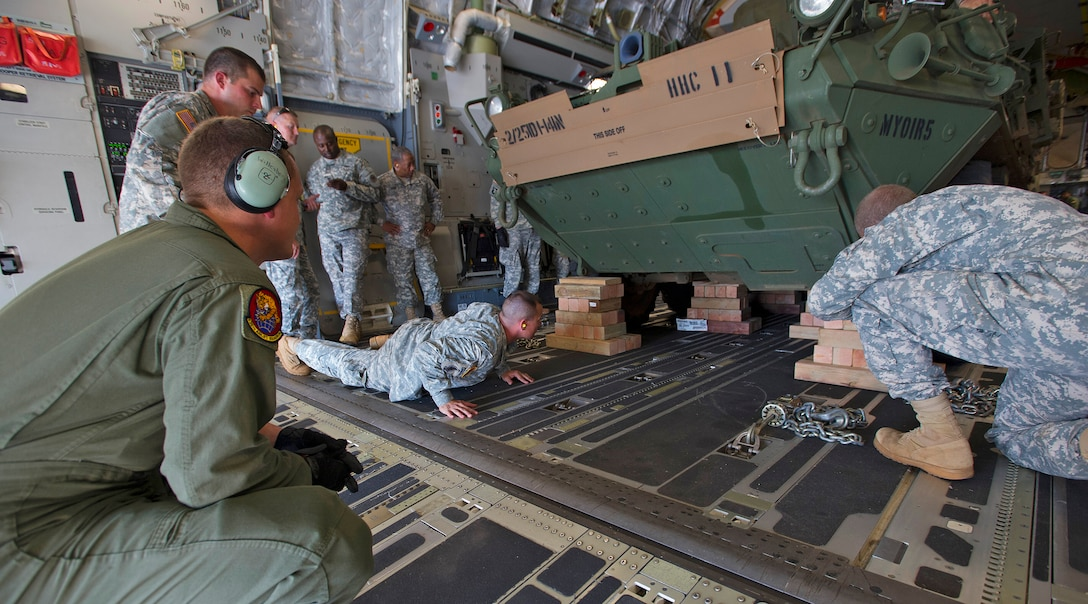 Senior Airman Jacob Willenborg (left), 535th Airlift Squadron loadmaster, helps secure the load of a Stryker medical evacuation vehicle assigned to the 1st Battalion, 14th Infantry, 2nd Stryker Brigade Combat Team, aboard a C-17 Globemaster III during a validation exercise on the flightline at Joint Base Pearl Harbor Hickam, Hawaii, Oct. 17, 2013. The Stryker is used to provide quick response maneuvering capability, enhanced survivability and lethality and expand fight versatility.