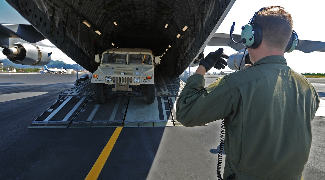 Senior Airman Jacob Willenborg, 535th Airlift Squadron loadmaster, guides a Stryker and trailer aboard a C-17 Globemaster III at Joint Base Pearl Harbor Hickam, Hawaii, Oct. 17, 2013. The vehicle was loaded as part of a validation exercise, which tested the 2nd Stryker Brigade Combat Team's ability to load their interim armored vehicles onto C-17s and fly them to the Pohakuloa Training Area in Kona, Hawaii.