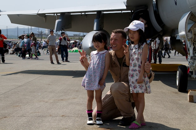 Capt. Timothy Farag, Marine Fighter Attack Squadron 242 pilot, poses for a picture with Japanese children during Friendship Day here May 5, 2012. Static displays and booths filled with food, clothing and other items blanketed the flight line along with more than 285,000 spectators, some traveling hundreds of miles to participate in the air show.
