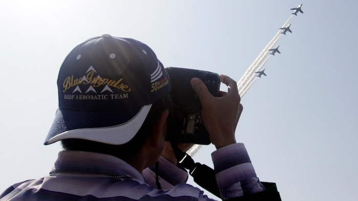 A Japanese spectator takes a photo of Blue Impulse during Friendship Day 2012 here, May 5, 2012. Friendship Day brought more than 285,000 spectators aboard the station to partake in static displays, American and Japanese vendors and a day-long air show.