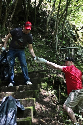 Lance Cpl. Jeffery Avery, station Provost Marshal's Office military police officer, hands a piece of trash to Pfc. Ricardo Atorgaortiz, Marine Aviation Logistics Squadron 12 Consolidated Automated Support System test station advanced maintenance technician, during the Marine Lounge Futashika River cleanup, May 18.