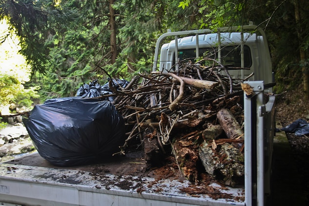 Marine Aviation Logistics Squadron 12 and Headquarters and Headquarters Squadron Marines worked together to gather wood, brush and trash at the Futashika River, May 18. The Marine Lounge hosted the river cleanup and together volunteers and workers gathered two truck loads of wood and approximately 20 bags of trash and brush.
