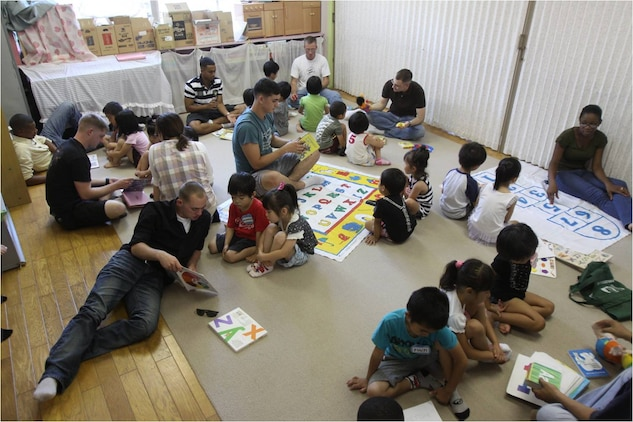 """Community-relations event volunteers sit with children at the Josho Hoikuen Preschool July 17, 2012, as the volunteers teach the children the English alphabet and numbers. Approximately 32 volunteers spent the morning with the children, reading and teaching them English and playing an assortment of games such as """"Duck, duck, goose"""" and """"Head and Shoulders."""""""