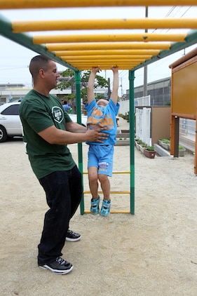 Hugo Giraldo, community relations volunteer, helps a child across a monkey bar during a community relations event at the Higashi Hoikuen Preschool in Iwakuni June 15, 2012. After the official relay was concluded, the children grabbed several of the volunteers and took them to different points on the playground. At the morning's conclusion, the children said goodbye in Japanese and for the volunteers to come again. The volunteers replied back saying they would.