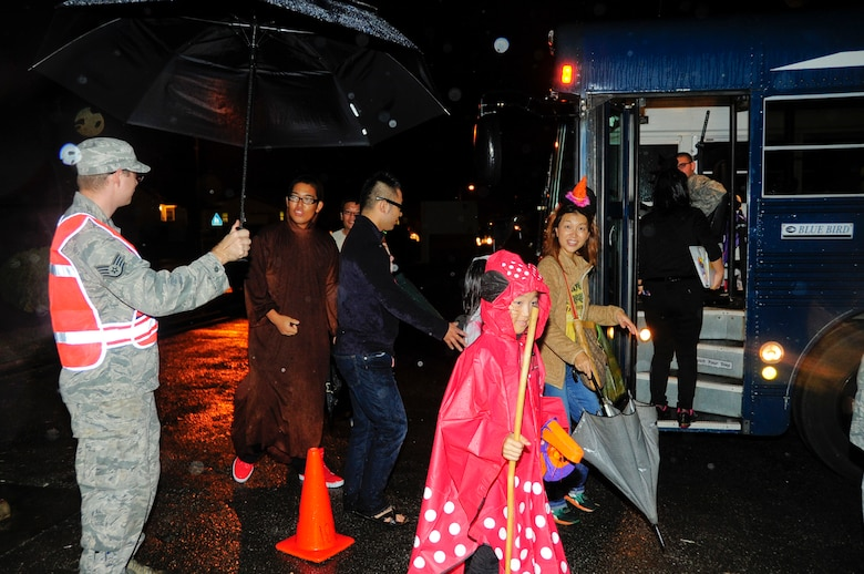 Staff Sgt. Christopher Price, 18th Component Maintenance Squadron aerospace propulsion specialist and Pumpkin Patrol volunteer, holds an umbrella for local national trick-or-treaters during Halloween on Kadena Air Base, Japan, Oct. 31, 2013. Kadena Air Base hosted more than 180 local community members for the Halloween festivities. (U.S. Air Force photo by Staff Sgt. Darnell T. Cannady)