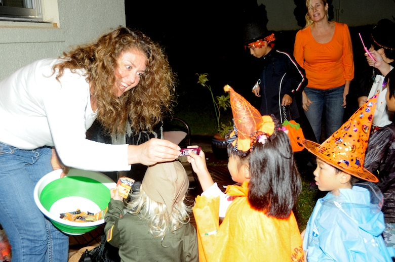 Kathleen Roesti hands out candy to local national trick-or-treaters during Halloween on Kadena Air Base, Japan, Oct. 31, 2013. Trick-or-treaters collected candy from families in the base housing areas. Some candy was donated through donation bins to be handed out in the base housing areas. (U.S. Air Force photo by Staff Sgt. Darnell T. Cannady)