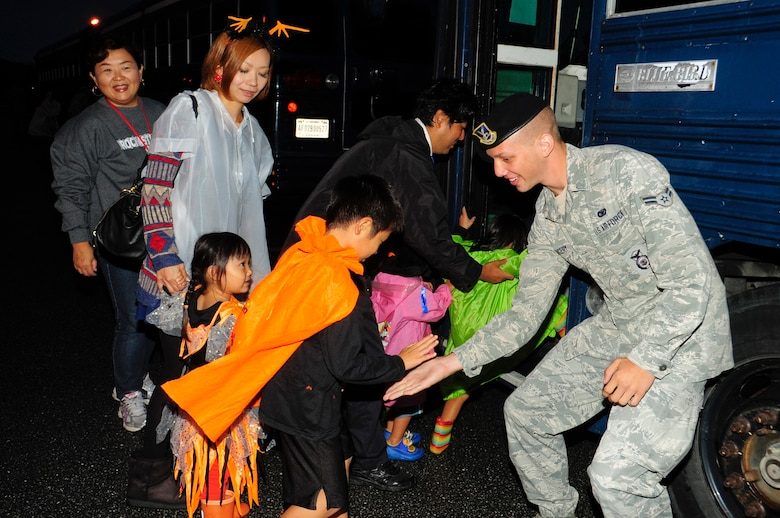 Airman 1st Class Colby Kingery, 18th Security Forces Squadron response force member and escort, greets local nations as they enter buses to begin trick-or-treating on Kadena Air Base, Japan, Oct. 31, 2013. Kadena Air Base bused local families to three base housing areas where they collected candy. The escorts assisted with security and the safety of the trick-or-treaters while they visited the base housing areas. (U.S. Air Force photo by Staff Sgt. Darnell T. Cannady)