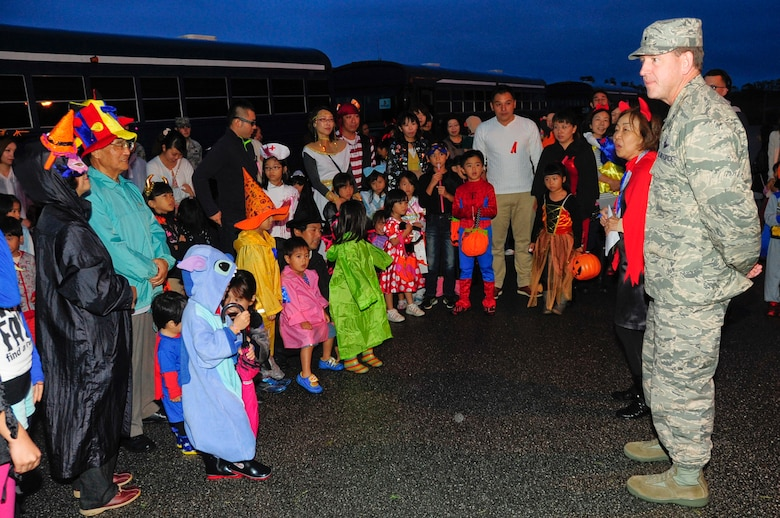 U.S. Air Force Brig. Gen. James Hecker, 18th Wing commander, greets the local national trick-or-treaters through translator Takako Fukuhara, 18th Wing Public Affairs community relations chief, during Halloween on Kadena Air Base, Japan, Oct. 31, 2013. Kadena hosted more than 180 local trick-or-treaters for these Halloween festivities. Kadena transported local community children on base to experience this holiday. (U.S. Air Force photo by Staff Sgt. Darnell T. Cannady)