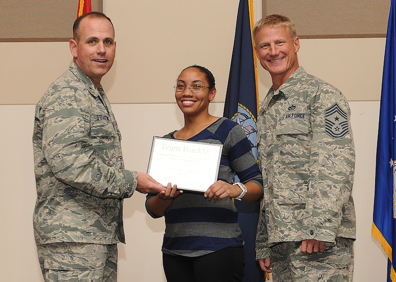 Courtney Richard, 460th Mission Support Group, center, receives the Civilian of the Quarter Category 1 Supervisory Award during the Quarterly 460th Space Wing and Team Buckley Awards Oct. 30, 2013, at the Leadership Development Center on Buckley Air Force Base, Colo. (U.S. Air Force photo by Senior Airman Marcy Copeland/Released)