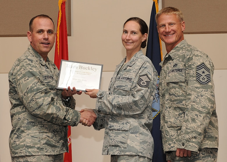 Master Sgt. Amy Reedy, Aerospace Data Facility-Colorado, center, receives the Senior Enlisted of the Quarter Award during the Quarterly 460th Space Wing and Team Buckley Awards Oct. 30, 2013, at the Leadership Development Center on Buckley Air Force Base, Colo. (U.S. Air Force photo by Senior Airman Marcy Copeland/Released)