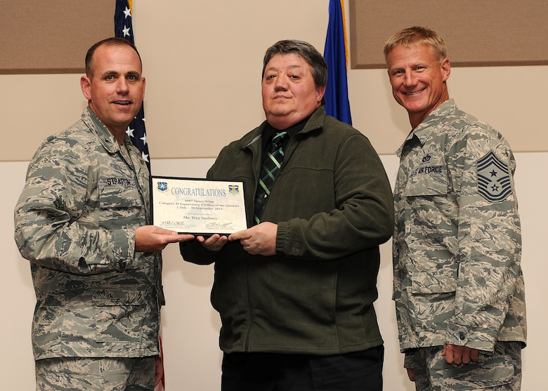 Troy Saxbury, 460th Operations Group, center, receives the Civilian of the Quarter, Category 2 Supervisory Award during the Quarterly 460th Space Wing and Team Buckley Awards Oct. 30, 2013, at the Leadership Development Center on Buckley Air Force Base, Colo. (U.S. Air Force photo by Senior Airman Marcy Copeland/Released)