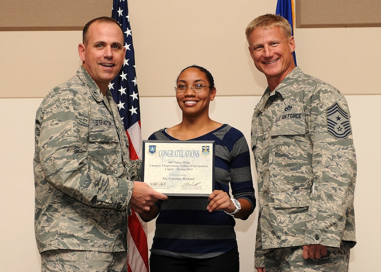 Courtney Richard, 460th Mission Support Group, center, receives the Civilian of the Quarter, Category 1 Supervisory Award during the Quarterly 460th Space Wing and Team Buckley Awards Oct. 30, 2013, at the Leadership Development Center on Buckley Air Force Base, Colo. (U.S. Air Force photo by Senior Airman Marcy Copeland/Released)