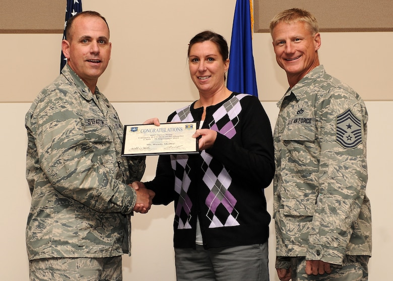 Wendy Medley, 460th Space Wing, center, receives the Civilian of the Quarter, Category 2 Award during the Quarterly 460th Space Wing and Team Buckley Awards Oct. 30, 2013, at the Leadership Development Center on Buckley Air Force Base, Colo. (U.S. Air Force photo by Senior Airman Marcy Copeland/Released)
