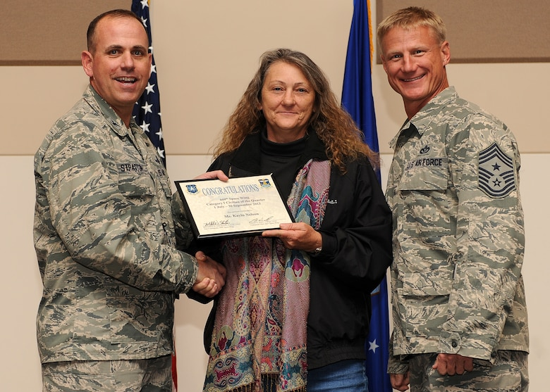 Kayln Nelson, 460th Mission Support Group, center, receives the Civilian of the Quarter, Category 1 Award during the Quarterly 460th Space Wing and Team Buckley Awards Oct. 30, 2013, at the Leadership Development Center on Buckley Air Force Base, Colo. (U.S. Air Force photo by Senior Airman Marcy Copeland/Released)