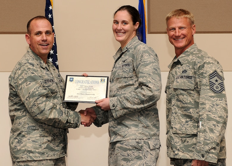 1st Lt. Mary Dunsworth, 460th Space Wing Staff, center, receives the Company Grade Officer of the Quarter Award during the Quarterly 460th Space Wing and Team Buckley Awards Oct. 30, 2013, at the Leadership Development Center on Buckley Air Force Base, Colo. (U.S. Air Force photo by Senior Airman Marcy Copeland/Released)