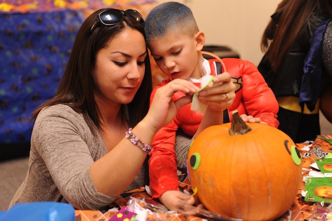 Nicole Lee, spouse of Staff Sgt. Matthew Lee, 819th RED HORSE Squadron member, and her son, Matthew, cover a pumpkin with stickers and various decorations at the pumpkin decorating station during the fall festival. Children and their families enjoyed various games, food and beverages at the annual event. (U.S. Air Force photo/Senior Airman Katrina Heikkinen)