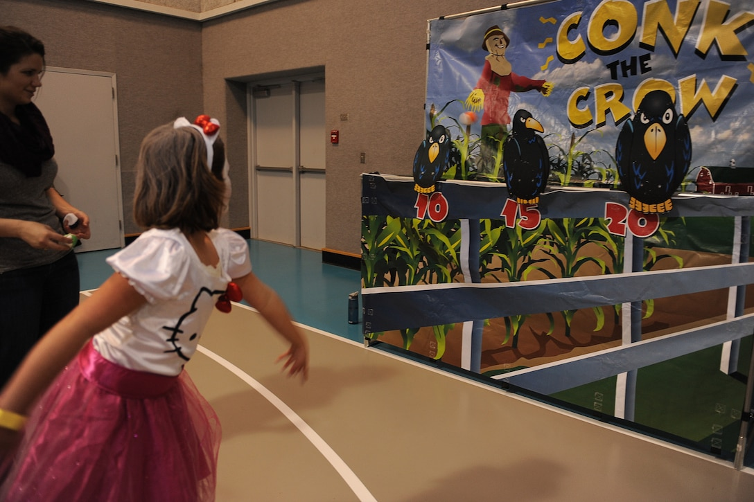A girl dressed as Hello Kitty throws a ball at a crow at the conk the crow station during the annual Malmstrom Youth Center Fall Festival on Oct. 25. Children of all ages attended the event in costume and were awarded prizes by age categories for the best costumes. (U.S. Air Force photo/Senior Airman Katrina Heikkinen)