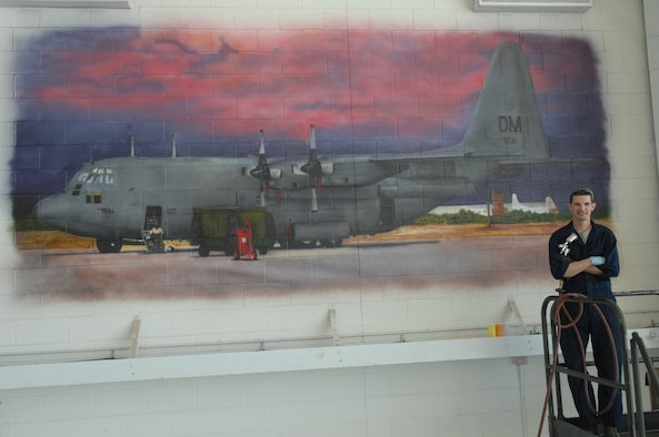 Senior Airman Patrick Corcoran, 755th Aircraft Maintenance Squadron propulsion technician, stands in front of a mural he airbrushed at Davis-Monthan Air Force Base, Ariz., Oct. 17, 2013. The mural took him about six weeks to complete and is the second of five murals be painted in the 755th AMXS hanger. (U.S. Air Force photo by Airman 1st Class Betty R. Chevalier/released)
