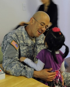 U.S. Army Sgt. David Hong, Fort Eustis chaplain assistant, talks with his daughter, Mary, after work at Fort Eustis, Va., Oct. 21, 2013. Mary's sister, Sophia, has Dravet syndrome, a rare form of intractable epilepsy that begins in infancy and causes severe seizures and delayed development. (U.S. Air Force photo by Airman 1st Class Austin Harvill/Released)