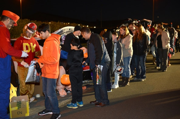 """SPANGDAHLEM AIR BASE, Germany – Parents take their children through a parking lot for """"trunk or treating"""" at Club Eifel Oct. 30, 2013. Children were dressed in costumes and walked through the parking lot collecting candy from the community members from their decorated cars' trunks. (U.S. Air Force photo by Airman 1st Class Kyle Gese/Released)"""