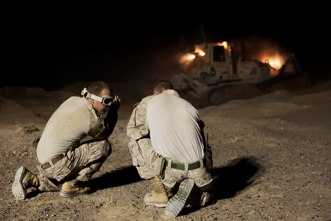 Two combat engineers with Combat Logistics Regiment 2, Regional Command (Southwest), discuss methods for erecting a new guard tower at Camp Dwyer, Afghanistan, Aug. 12, 2013. A platoon of combat engineers and heavy equipment operators worked through the night and endured the constant sting of blowing sand to erect a new guard tower at the base.