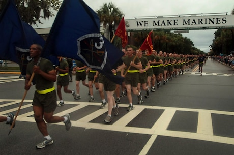 "New Marines of Kilo Company, 3rd Recruit Training Battalion, run under the ""We Make Marines"" sign during a traditional motivational run through the streets of Parris Island, S.C., on Aug 15, 2013. The run took place before the new Marines had a few hours to reunite with their friends and families for the first time in more than 12 weeks. Kilo Company is scheduled to graduate Aug. 16, 2013. Parris Island has been the site of Marine Corps recruit training since Nov. 1, 1915. Today, approximately 20,000 recruits come to Parris Island annually for the chance to become United States Marines by enduring 13 weeks of rigorous, transformative training. Parris Island is home to entry-level enlisted training for 50 percent of males and 100 percent for females in the Marine Corps. (Photo by Cpl. Caitlin Brink)"