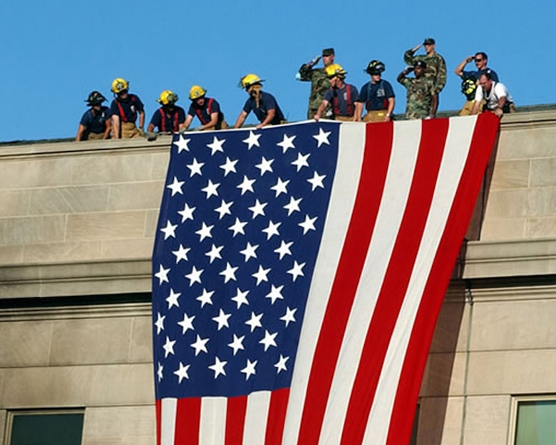Firefighters and U.S. Army Soldiers unfurl an American flag over the side of the Pentagon during the aftermath of the 9/11 terrorist attack against the building. The Pentagon was the third U.S. building to be struck by al-Qaida militants, Sept. 11, 2001. (Courtesy photo from Reuters/Released)