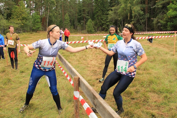 Maj Maiya Anderson (USAF) (left) hands off to LT Virginia Debons (Navy) in the Women's relay at the 2013 CISM World Orienteering Military Championship hosted by the Swedish Armed Forces in Eksjo, Sweden from 26 August to 1 September.