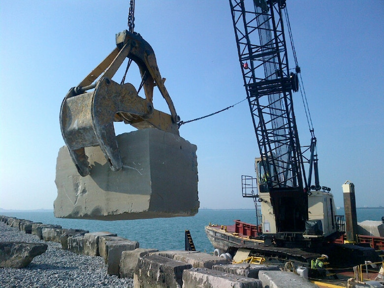 The Manitowoc Crane Barge lays down a cut stone, weighing up to nine tons, at the Calumet Harbor breakwall during summer maintenance.