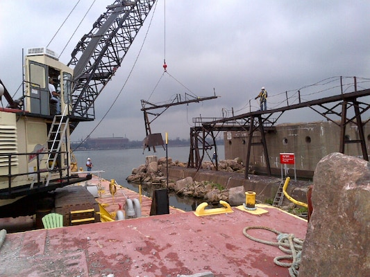 The Manitowoc crane barge removes part of the catwalk structure from the Indiana Harbor pier in East Chicago, Ind.