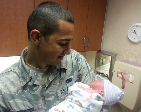 Airman 1st Class Timothy Pledger, 20th Aircraft Maintenance Unit electronic warfare journeyman, holds his daughter, Zoey, hours after delivering her himself Aug. 30, 2013. Pledger's flight to deploy to Guam had been delayed so he went home to be with his pregnant wife. Not long after he came home, she went into labor. In less than an hour, Pledger and his wife welcomed in their new baby girl, Zoey, into the family. (Courtesy photo)